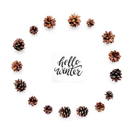 Hallo winter hand belettering. De winterpatroon met pinecones op witte hoogste mening als achtergrond.
