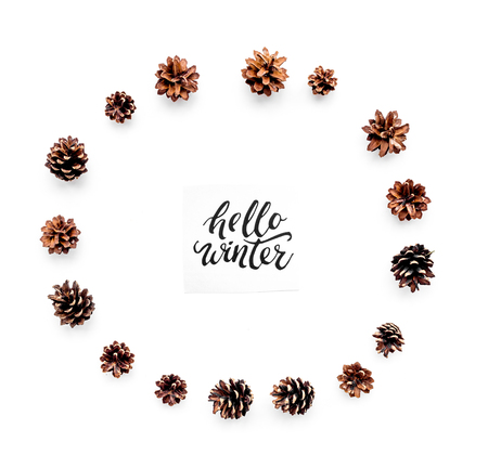 Hello winter hand lettering. Winter pattern with pinecones on white background top view.