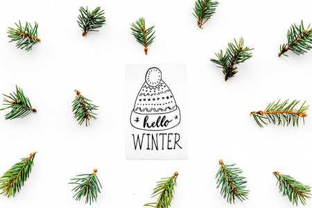 Hello winter hand lettering with hat icon. Winter pattern with spruce branches on white background top view