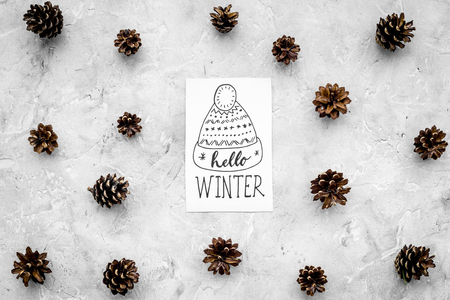 Hello winter hand lettering with hat icon. Winter pattern with pinecones on grey background top view. Banco de Imagens