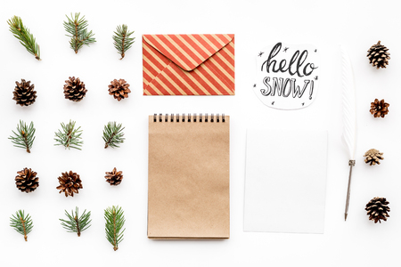 Write greetings. Envelope, paper, spruce branches and cones and hello snow hand lettering on white background top view pattern copyspace