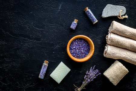 Set for foot spa with lavender. Flowers, spa salt, pumice stone, soap on black background top view copyspace