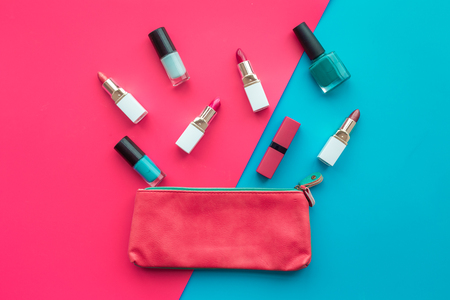 Lipsticks assorted colors and nail polish near cosmetic bag on blue and pink background top view