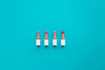 Lipsticks assorted colors on blue background top view.
