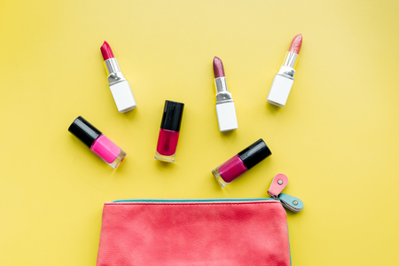Decorative cosmetics concept. Lipsticks assorted colors and nail polish near cosmetic bag on yellow background top view.