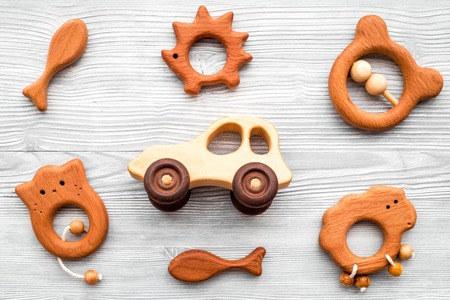 Cute wooden handmade toys for newborn on grey wooden background top view.