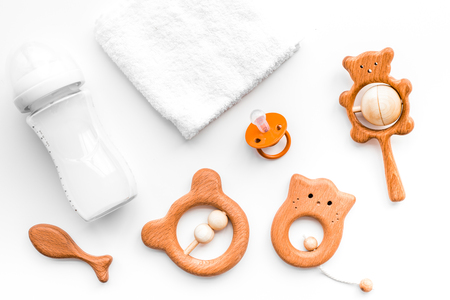 Baby accessories. Wooden toys, pacifier and bottle on white background top view. Stock Photo