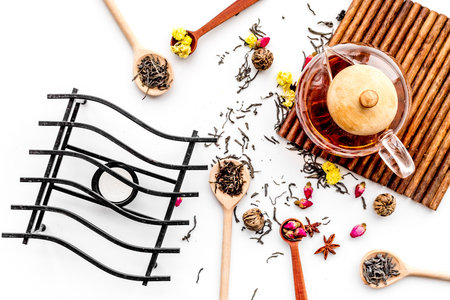 Brew tea with flowers and spices. Dried leaves and petals near tea pot on white background top view Stock Photo