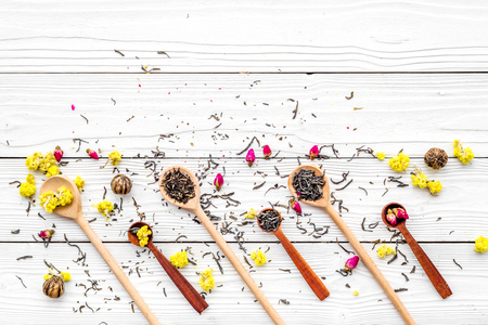 Aromatic tea. Wooden spoons with dried tea leaves, flowers and spices on white wooden background top view copyspace