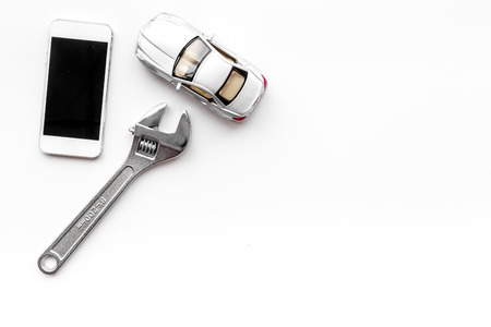 Choose car service. Wrench near car toys and cell phone on white background top view copyspace Reklamní fotografie
