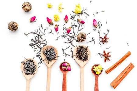Dried tea leaves near supplements like flowers and spices on white background top view.