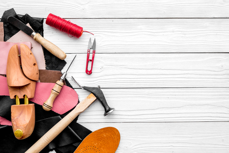 Shoemakers craft. Tools, wooden last, pieces of leather on white wooden background top view. Stock Photo