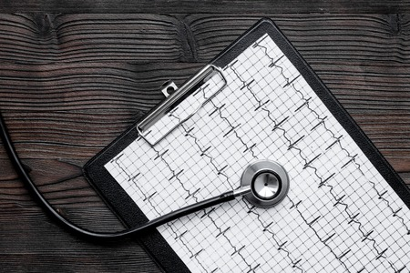 To diagnose heart disease. Cardiogram, stethoscope on white background top view