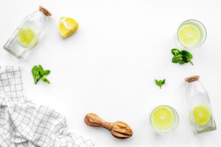 Prepare refreshing beverage lemonade. Lemons, juicer, bottle on white background top view copyspace