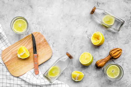 Prepare refreshing beverage lemonade. Lemons, juicer, bottle, knife, cutting board on grey stone background top view copyspace Stock Photo