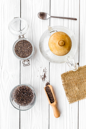 Brew chia seeds. Jar with seeds, scoop, bowl, tea pot with hot water. White wooden background top view