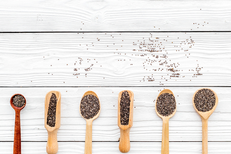 Superfood chia seeds in a wooden spoon and scoop on white wooden background top view copyspace Stock Photo