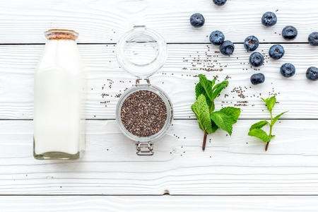 Eat chia seeds for breakfast with yogurt, blueberry and mint. White wooden background top view Stock Photo