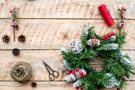 크리스마스 화환을 만드십시오. 가문비 나무 나뭇 가지, 콘, 스레드, 꼬기, sciccors 빛 나무 배경 상위 뷰 스톡 콘텐츠