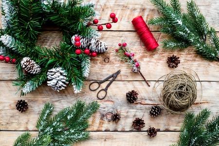 Machen Sie Weihnachtskranz. Fichtenzweige, Kegel, Threads, Schnur, Sciccors auf Draufsicht des hellen hölzernen Hintergrundes Standard-Bild - 90185940