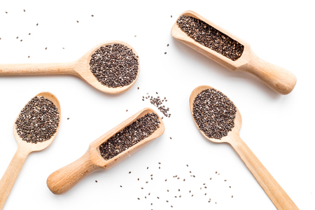 Superfood chia seeds in a wooden spoon and scoop on white background top view