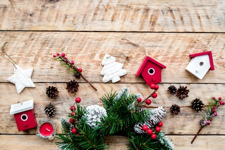 Decorate house for Christmas. Wreath and toys on light wooden background top view copyspace