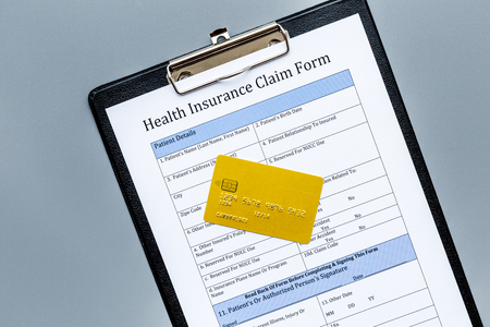 Buy health insurance. Document, bank card on dark grey background top view