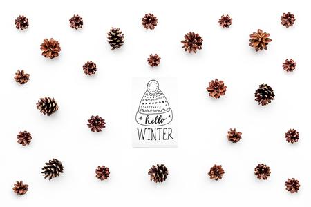 Hallo winter hand belettering met hoed pictogram. De winterpatroon met denneappels op witte hoogste mening als achtergrond Stockfoto
