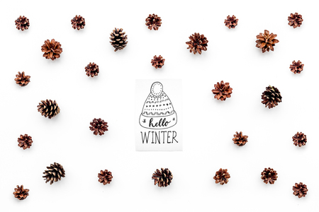 Hello winter hand lettering with hat icon. Winter pattern with pine cones on white background top view Stock Photo