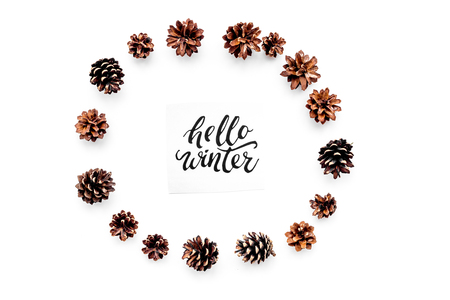 Hello winter hand lettering. Winter pattern with pinecones on white background top view