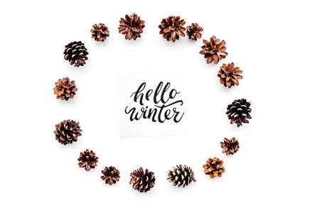 Hallo winter hand belettering. De winterpatroon met pinecones op witte hoogste mening als achtergrond Stockfoto - 90185796