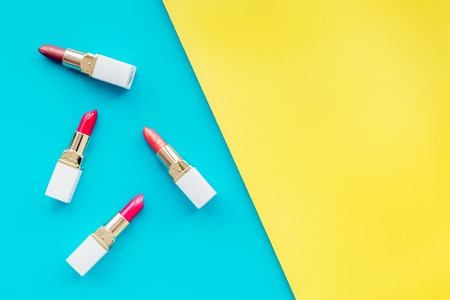 Lipsticks assorted colors on yellow and blue background top view copyspace