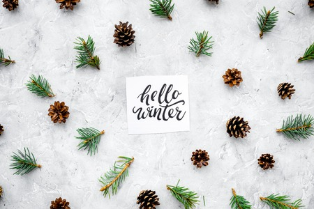Hello winter hand lettering. Winter pattern with pinecones and spruce branch on grey background top view