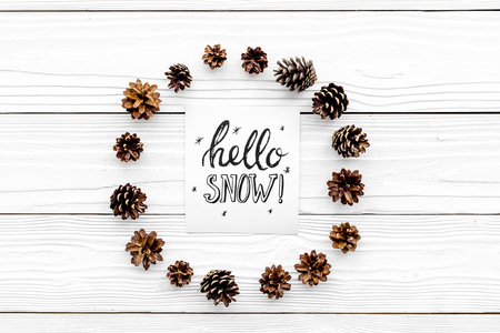 Hello snow hand lettering. Winter pattern with pinecones on white wooden background top view copyspace