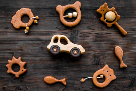 Cute wooden handmade toys for newborn on dark wooden background top view Stok Fotoğraf