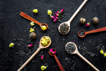 Aromatic tea. Wooden spoons with dried tea leaves, flowers and spices on black background top view