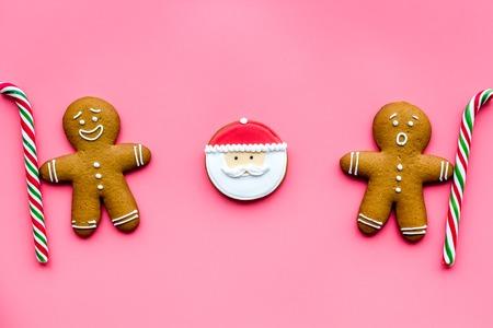 ピンク色の背景上に正月の食事のジンジャーブレッドマン クッキーを表示します。