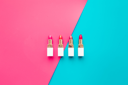 Lipsticks assorted colors on blue and pink background top view copyspace