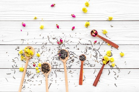 Aromatic tea. Wooden spoons with dried tea leaves, flowers and spices on white wooden background top view Stock Photo
