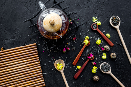 Brew the aromatic tea. Tea pot near wooden spoons with dried tea leaves, flowers and spices on black wooden background top view mockup