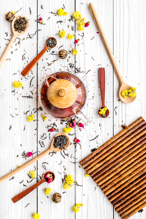 Brew the aromatic tea. Tea pot near wooden spoons with dried tea leaves, flowers and spices on white wooden background top view. Stock Photo