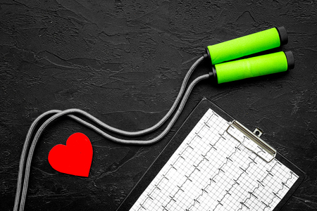 Prevent heart disease. Heart sign, cardiogram, jump rope on black background top view copyspace