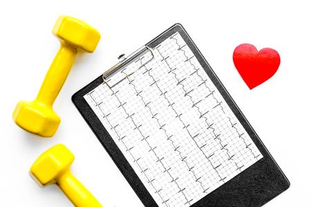 Prevent heart disease. Heart sign, cardiogram and dumbbells on white background top view. Stock Photo
