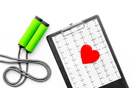 Prevent heart disease. Heart sign, cardiogram, jump rope on white background top view Stock Photo