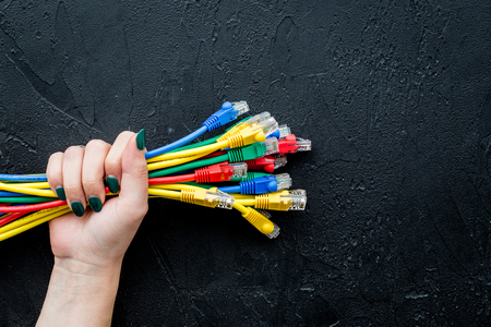 Hand hold network wires assorted colors with tips on black background top view