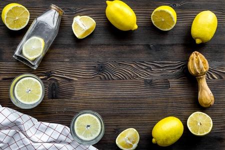Prepare refreshing beverage lemonade. Lemons, juicer, bottle on dark wooden background top view copyspace