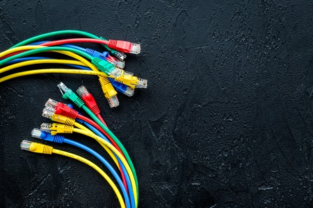 Network wires assorted colors with tips on black background top view copyspace