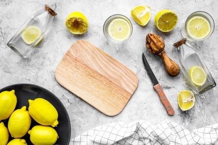 Prepare refreshing beverage lemonade. Lemons, juicer, bottle, knife, cutting board on grey stone background top view mockup Stock Photo