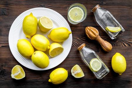 Fresh homemade lemonade. Lemons, juicer, glass for beverage on dark wooden background top view