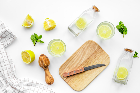 Prepare refreshing beverage lemonade. Lemons, juicer, bottle, knife, cutting board on white background top view